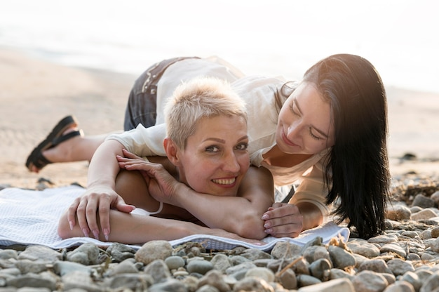 ビーチで楽しんで若いレズビアンのカップル