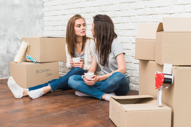 Young lesbian couple holding coffee cup in hands looking at each other sitting among the cardboard boxes