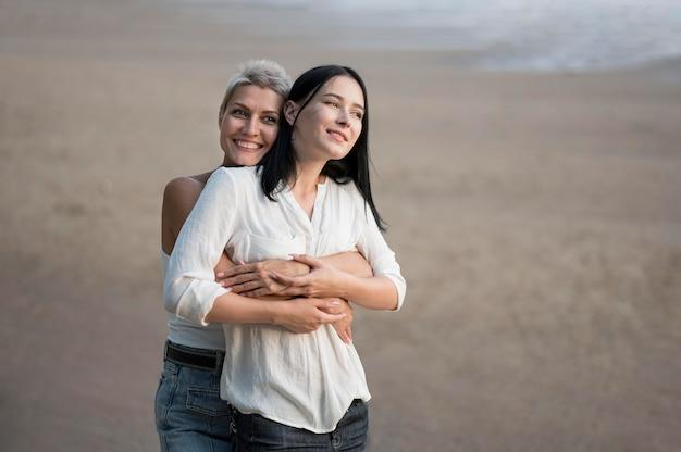 海の側で抱き締める若いレズビアンのカップル