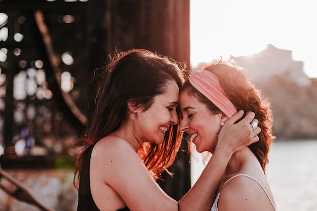 Young lesbian couple hugging at sunset outdoors