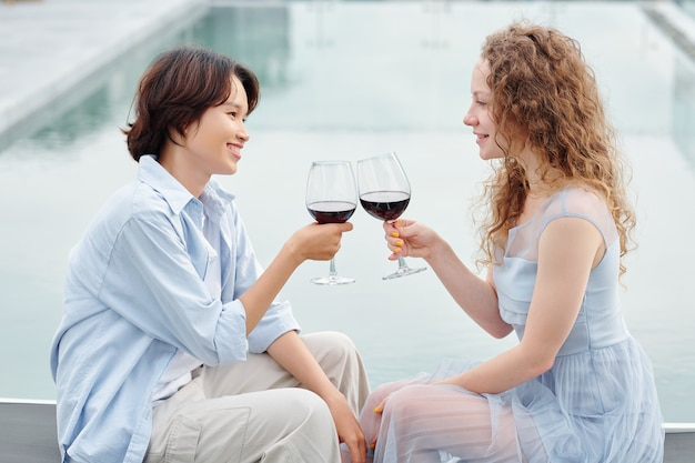 Young lesbian couple in love drinking red wine when having romantic date outdoor