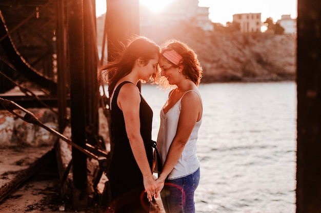 Young lesbian couple at sunset at the beach