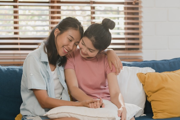 Young lesbian lgbtq asian women couple hug and kiss at home