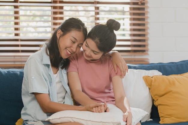 Young lesbian lgbtq asian women couple hug and kiss at home