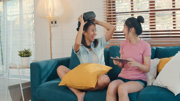 Young lesbian lgbtq asian women couple using tablet at home