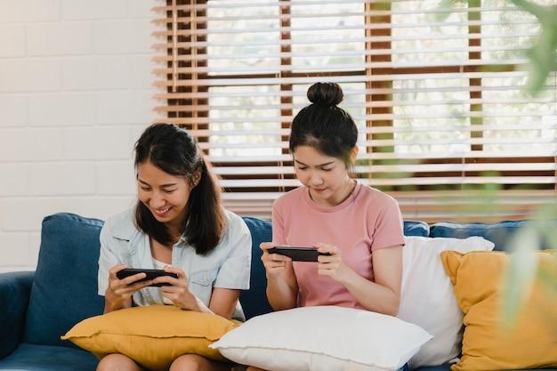 Молодые лесбиянки lgbtq женщины соединяются дома с помощью мобильного телефона