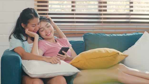 Young lesbian lgbtq women couple using mobile phone at home.