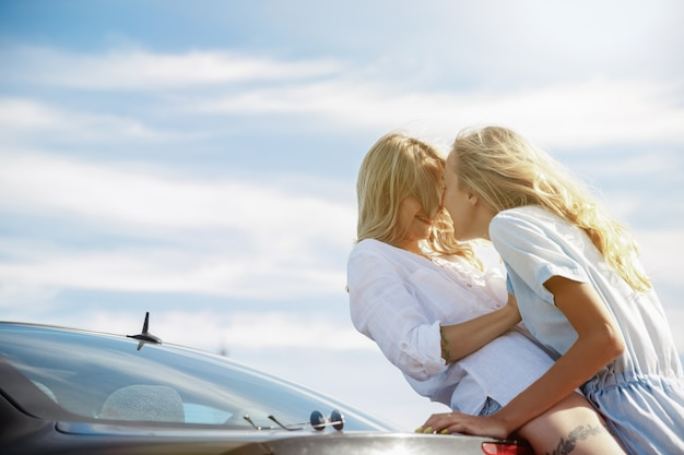 The young lesbian's couple broke down the car while traveling on the way to rest. kissing and cuddling on the car's trunk. relationship, troubles on the road, vacation, holidays, honeymoon concept.