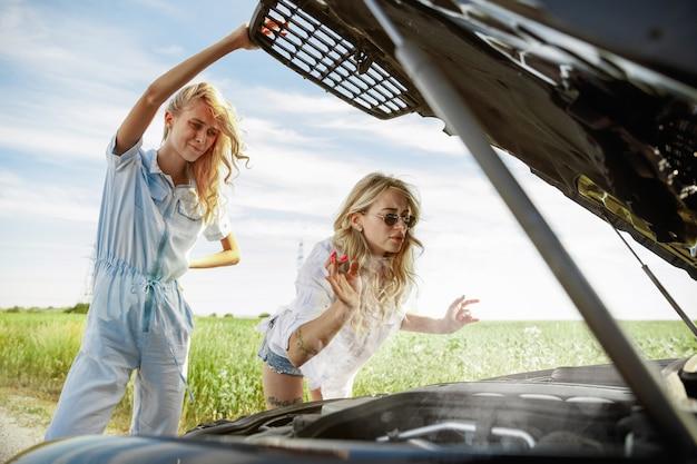 晴れた日に車で休暇旅行に行く若いレズビアンのカップル