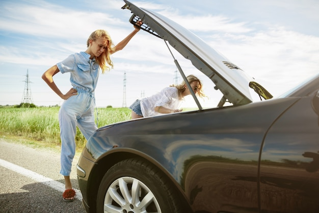 Young lesbian's couple going to vacation trip on the car in sunny day