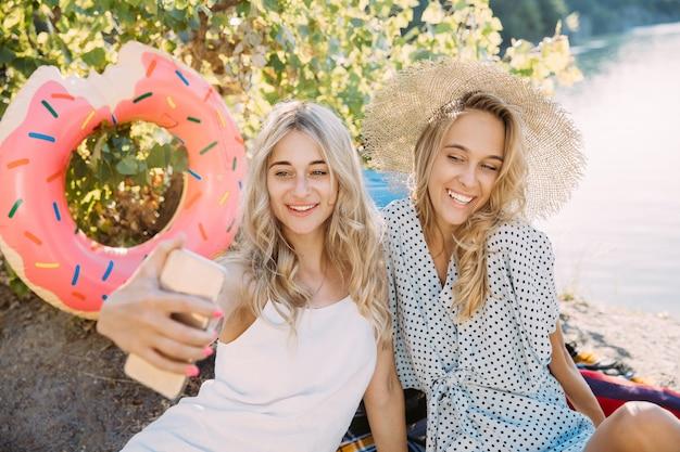 Пара молодых лесбиянок веселится на берегу реки в солнечный день. женщины вместе проводят время на природе. пьет вино, делает селфи. концепция отношений, любви, лета, выходных, медового месяца.