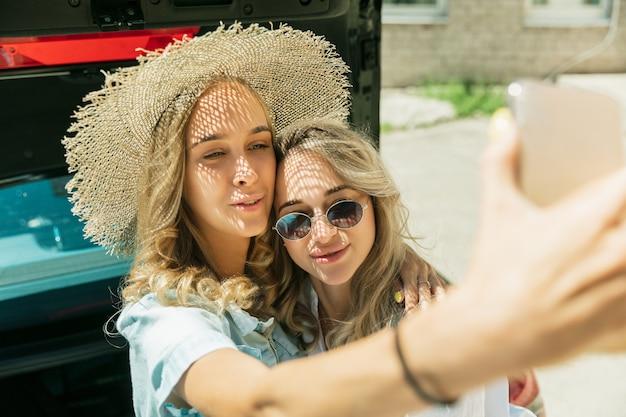 Пара молодых лесбиянок готовится к поездке в отпуск на машине в солнечный день. улыбающиеся и счастливые девушки перед тем, как отправиться в море или океан. концепция отношений, любви, лета, выходных, медового месяца, отпуска.