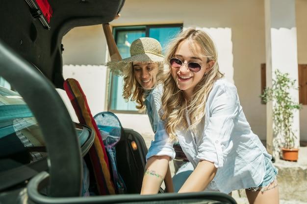 화창한 날에 차에서 휴가 여행을 준비하는 젊은 레즈비언의 커플