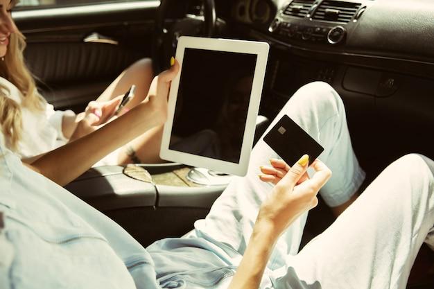 晴れた日に車で休暇旅行の準備をしている若いレズビアンのカップル
