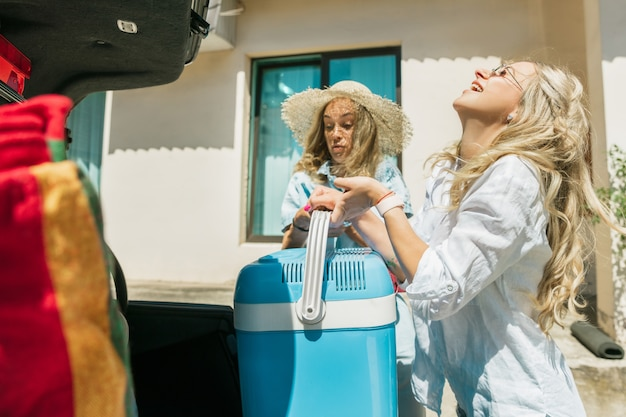 Young lesbian's couple preparing for vacation trip on the car in sunny day. smiling and happy girls before going to sea or ocean. concept of relationship, love, summer, weekend, honeymoon, vacation.