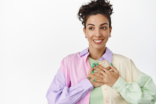 Young lesbian woman holding hand on heart, smiling happy and looking away at logo, being uplifted, pride and lgbtq concept on white isolated