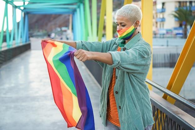 Young lesbian woman holding rainbow lgbt gay flag - focus on face