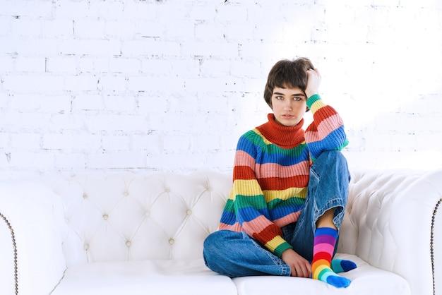 レインボーlgbtセーターの若いレズビアンの女性は、明るい部屋のソファに座って性的マイノリティの権利...