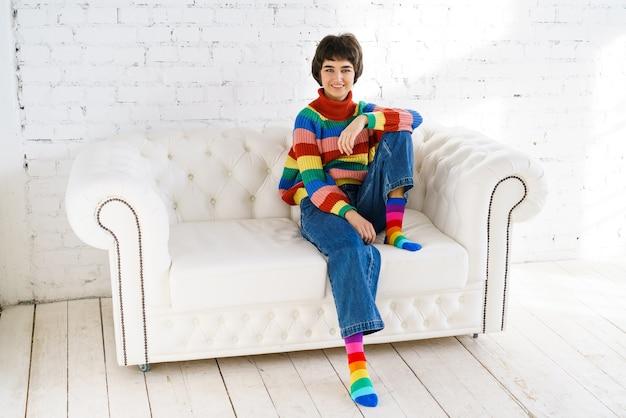 虹のlgbtセーターの若いレズビアンの女性は明るい部屋のソファに座っています。性的マイノリティの権利。ゲイやレズビアンへの自由恋愛。 lgbtコミュニティ。不平等抗議レインボーフラッグ