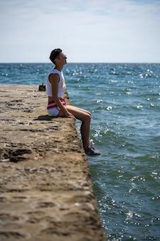 젊은 레즈비언 여자는 부두에 반바지와 신발을 신고 혼자 앉아 있습니다. 뒷모습. 여름 바다