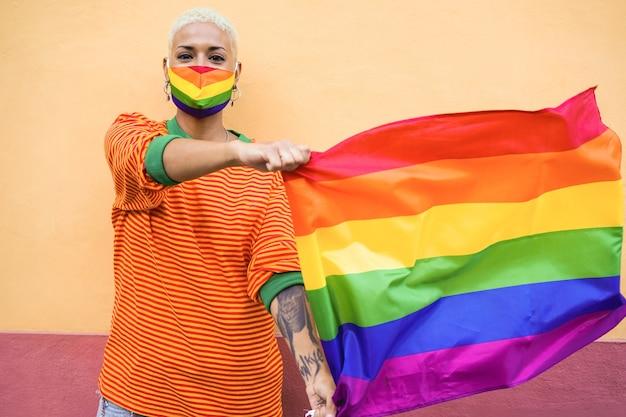 Молодая лесбиянка с радужной маской держит флаг лгбт