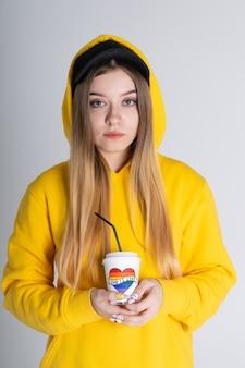 Грустная молодая лгбт-женщина в желтой толстовке с капюшоном держит чашку с радужным сердцем на сером фоне