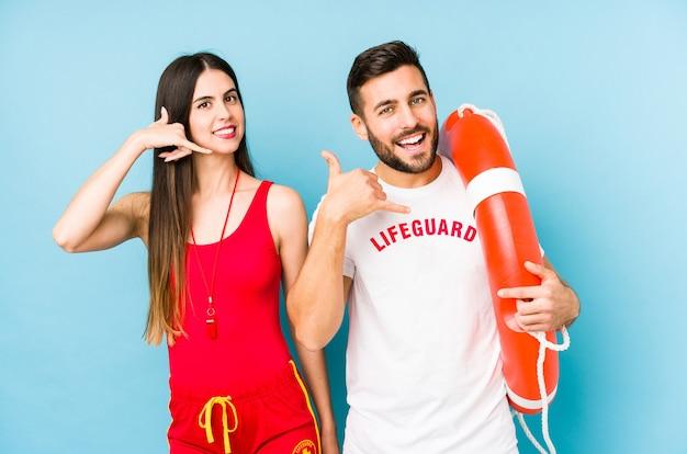 若いライフガードカップルが指で携帯電話のジェスチャーを示す分離。