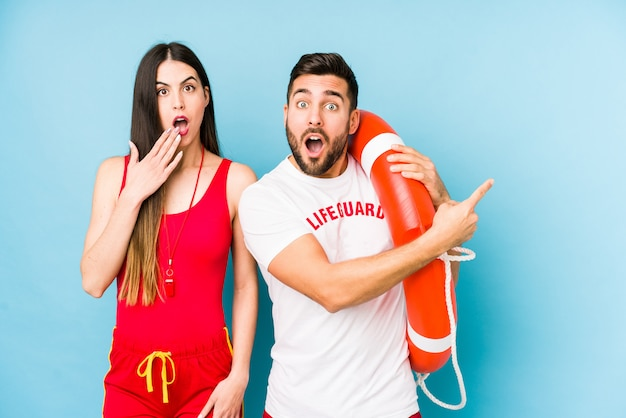 Young lifeguard couple pointing to the side
