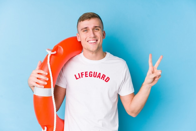 Young lifeguard man holding a rescue float joyful and carefree showing a peace symbol with fingers.