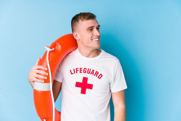 Young lifeguard man holding a rescue float looks aside smiling, cheerful and pleasant.