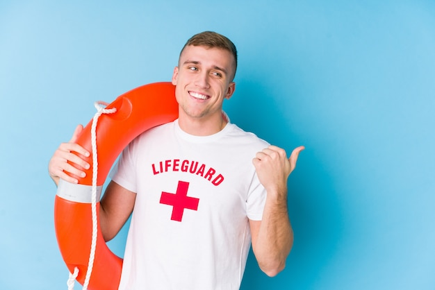 Young lifeguard man holding a rescue float points with thumb finger away, laughing and carefree.