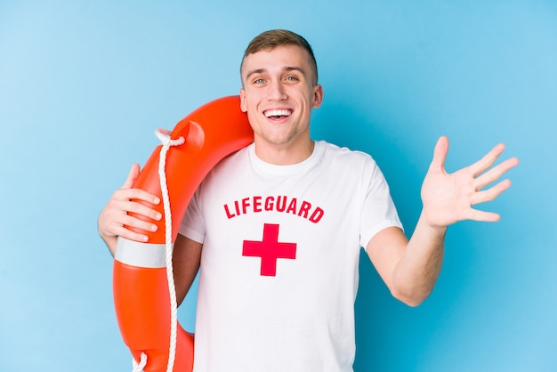 Young lifeguard man holding a rescue float receiving a pleasant surprise, excited and raising hands.