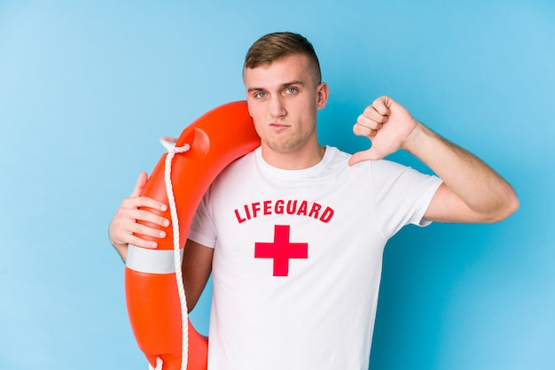 Young lifeguard man holding a rescue float showing a dislike gesture, thumbs down. disagreement concept.