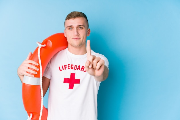 Young lifeguard man holding a rescue float showing number one with finger.