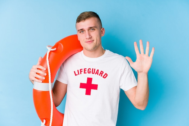 Young lifeguard man holding a rescue float smiling cheerful showing number five with fingers.