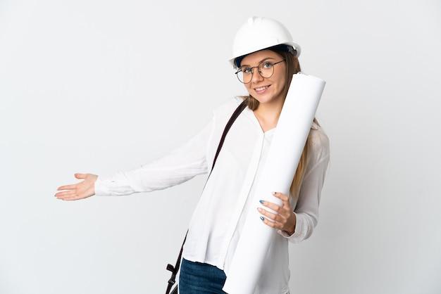 ヘルメットと白い背景で隔離の青写真を保持している若いリトアニアの建築家の女性は、来て招待するために手を横に伸ばします