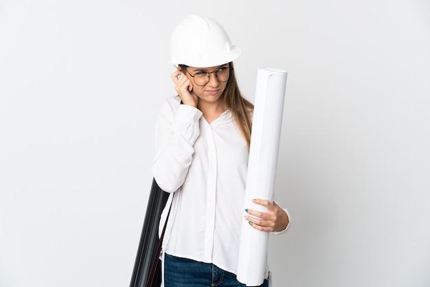ヘルメットと白い背景で隔離の青写真を保持している若いリトアニアの建築家の女性は欲求不満と耳を覆っています