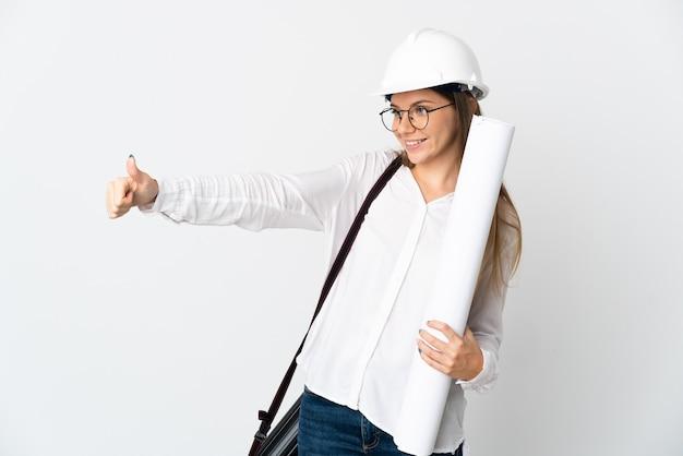 헬멧을 쓰고 흰색 배경에 격리된 청사진을 들고 엄지손가락을 치켜드는 젊은 리투아니아 건축가 여성