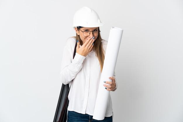ヘルメットと白い背景で隔離の青写真を保持している若いリトアニアの建築家の女性幸せと笑顔の手で口を覆う