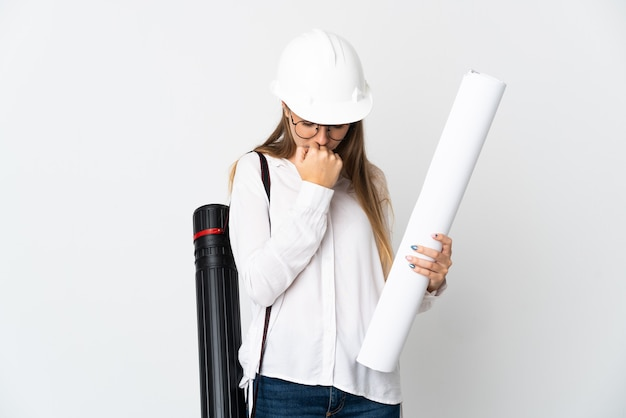 헬멧을 가진 젊은 리투아니아 건축가 여자와 의심을 갖는 흰색 배경에 고립 된 청사진을 들고