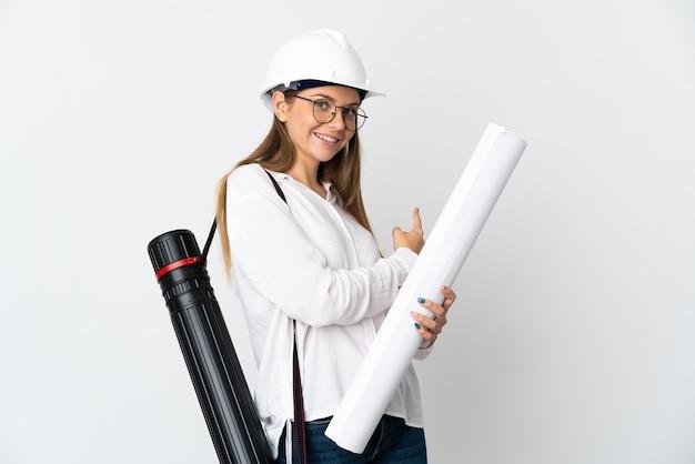 Молодой литовский архитектор женщина в шлеме и держит чертежи, изолированные на белом фоне, указывая назад