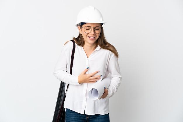 ヘルメットと白い背景で隔離の青写真を保持している若いリトアニアの建築家の女性はたくさん笑っています