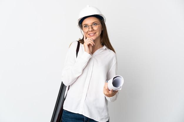 Молодой литовский архитектор женщина в шлеме и держит чертежи, изолированные на белом, думая об идее, глядя вверх