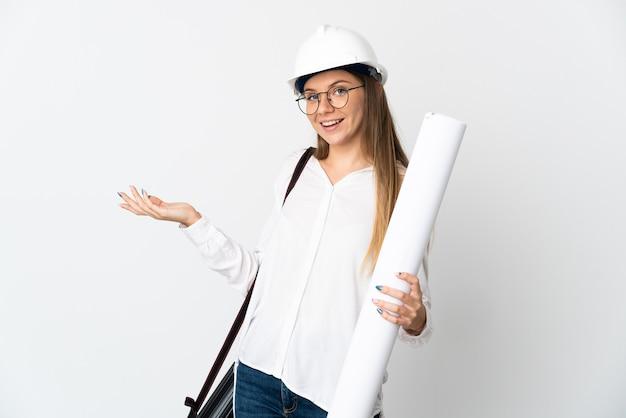 헬멧과 청사진을 들고 젊은 리투아니아 건축가 여자와 서 초대를 위해 손을 옆으로 확장 흰색 벽에 고립