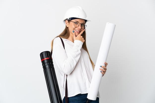 헬멧을 가진 젊은 리투아니아 건축가 여자와 청사진을 들고 행복하고 웃는 흰 벽에 고립