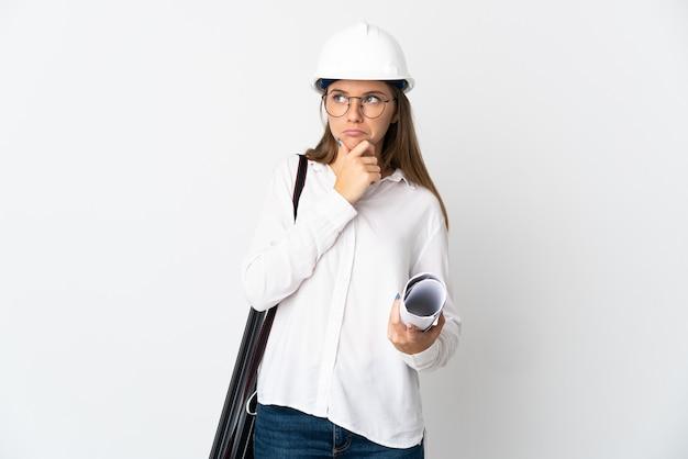 헬멧을 가진 젊은 리투아니아 건축가 여자와 의구심을 갖는 흰 벽에 고립 된 청사진을 들고