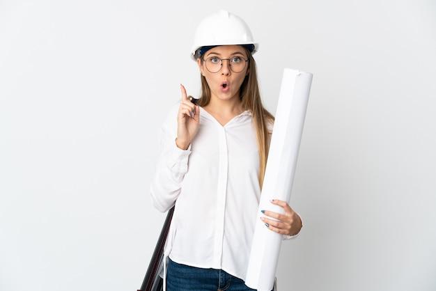 헬멧을 가진 젊은 리투아니아 건축가 여자와 흰 벽에 고립 된 청사진을 들고 손가락을 들어 올리면서 솔루션을 실현하려는 의도