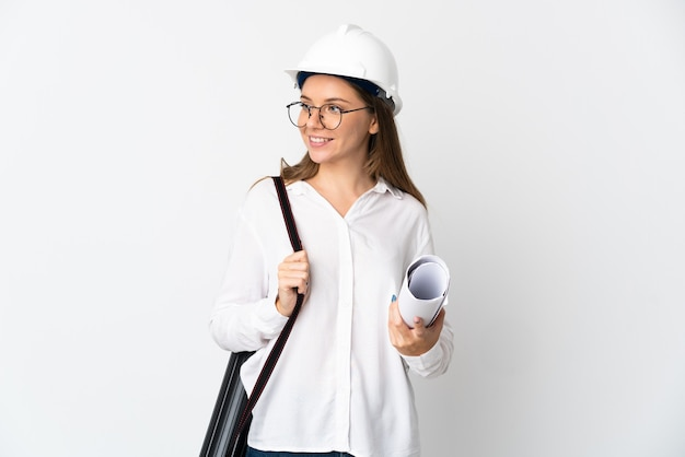 헬멧과 측면을 찾고 흰 벽에 고립 된 청사진을 들고 젊은 리투아니아 건축가 여자