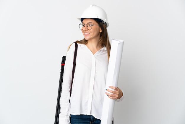헬멧과 흰색 벽에 고립 된 청사진을 들고 젊은 리투아니아 건축가 여자 측면을 찾고 웃