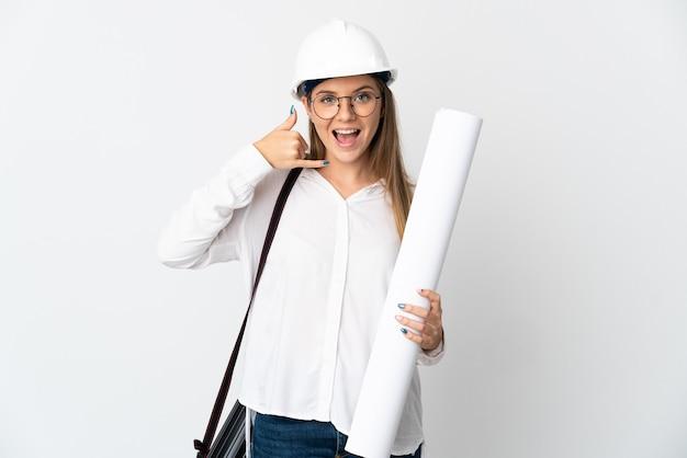 Молодой литовский архитектор женщина в шлеме и держит чертежи, изолированные на белой стене, делая жест телефона